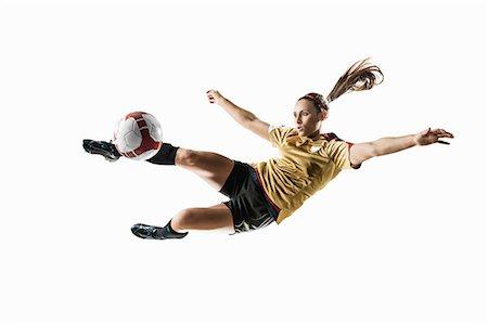 footballeur - Studio shot of young female soccer player kicking ball mid air Stock Photo - Premium Royalty-Free, Code: 614-07444392