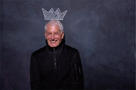 Portrait of senior man in front of chalked crown on blackboard Stock Photo - Premium Royalty-Free, Code: 614-07443985