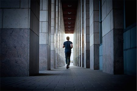 Young man running along urban sidewalk Stock Photo - Premium Royalty-Free, Code: 614-07453274