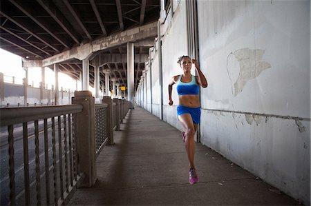 Young woman running on urban bridge Stock Photo - Premium Royalty-Free, Code: 614-07453280