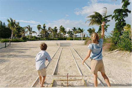 Brother and sister playing horseshoe game, Providenciales, Turks and Caicos Islands, Caribbean Stock Photo - Premium Royalty-Free, Code: 614-07453292