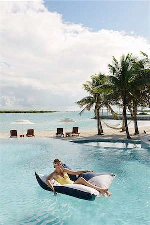 pool - Young woman reclining on airbed in swimming pool, Providenciales, Turks and Caicos Islands, Caribbean Stock Photo - Premium Royalty-Free, Code: 614-07453416