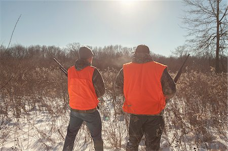 Mid adult man and teenage son hunting in Petersburg State Game Area, Michigan, USA Stock Photo - Premium Royalty-Free, Code: 614-07453425