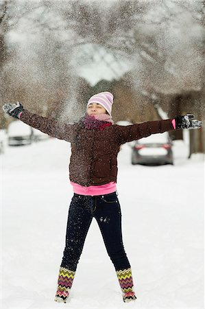 Teenage girl throwing powdered snow mid air in street Stock Photo - Premium Royalty-Free, Code: 614-07453435