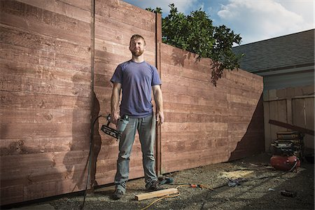 Portrait of joiner in backyard in front of new fence Stock Photo - Premium Royalty-Free, Code: 614-07486895