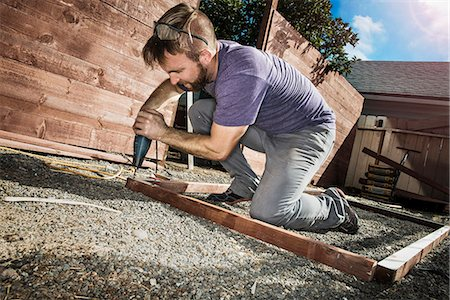 drilling - Joiner in backyard drilling wood framework Stock Photo - Premium Royalty-Free, Code: 614-07486891