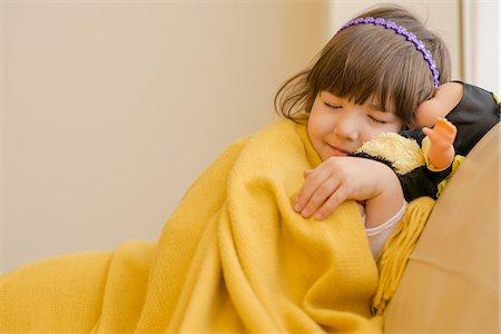 Young girl lying on sofa pretending to sleep Stock Photo - Premium Royalty-Free, Code: 614-07486907