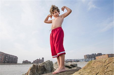 Boy at the coast showing off his arm muscles, Long Beach, New York State, USA Stock Photo - Premium Royalty-Free, Code: 614-07486917