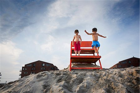 Two boys jumping off red notice board, Long Beach, New York State, USA Stock Photo - Premium Royalty-Free, Code: 614-07486919