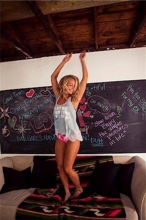Young woman dancing on sofa Stock Photo - Premium Royalty-Free, Code: 614-07486968