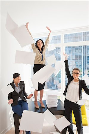 Three young businesswoman throwing papers mid air Stock Photo - Premium Royalty-Free, Code: 614-07486987