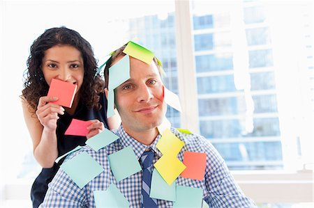 self adhesive note - Female office worker covering male colleague with sticky notes Stock Photo - Premium Royalty-Free, Code: 614-07487004