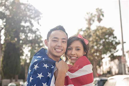 Portrait of a couple standing on street wrapped in American flag Stock Photo - Premium Royalty-Free, Code: 614-07487035