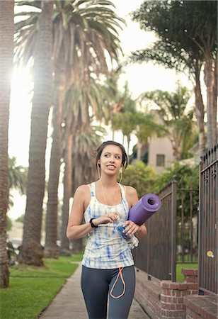 Young woman walking along sidewalk carrying yoga mat Stock Photo - Premium Royalty-Free, Code: 614-07487038