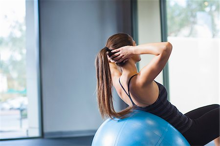 Young woman working out with gym ball Stock Photo - Premium Royalty-Free, Code: 614-07487110