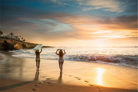 friendship - Surfers carrying surf board, walking along beach Stock Photo - Premium Royalty-Free, Code: 614-07487185