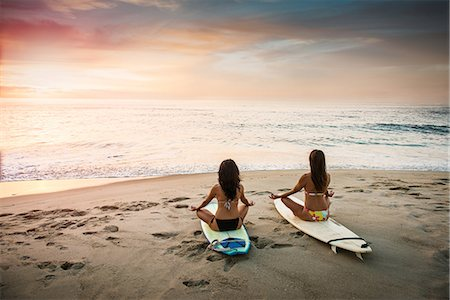 Two surfers, sitting on surfboards on beach, meditating Stock Photo - Premium Royalty-Free, Code: 614-07487181
