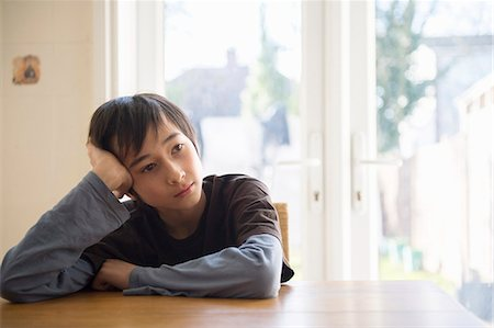 sad child sitting - Boy sitting at table, head resting in hand Stock Photo - Premium Royalty-Free, Code: 614-07487213