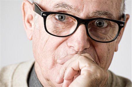 Portrait of senior man, hand on mouth Stock Photo - Premium Royalty-Free, Code: 614-07487224