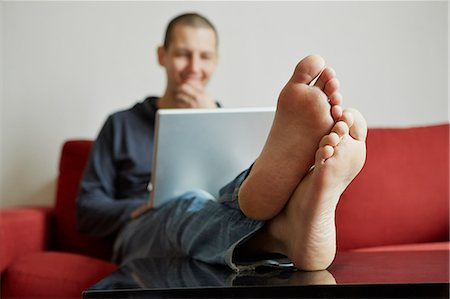 Mid adult man relaxing on sofa engrossed in laptop Stock Photo - Premium Royalty-Free, Code: 614-07587533