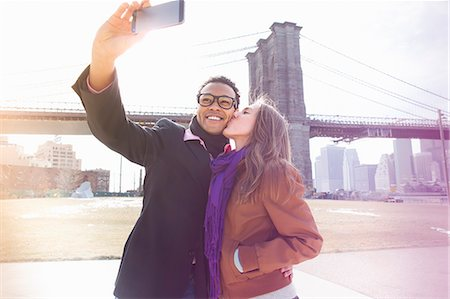 people and vacation - Young couple taking self portrait next to Brooklyn Bridge, New York, USA Stock Photo - Premium Royalty-Free, Code: 614-07587555
