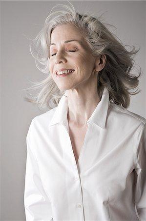 Mature woman smiling, eyes closed Stock Photo - Premium Royalty-Free, Code: 614-07587618
