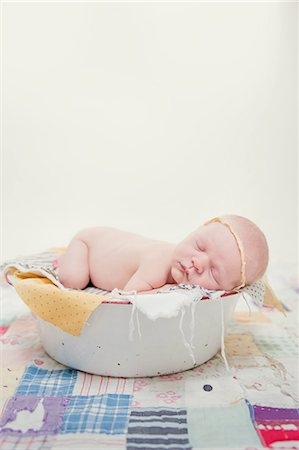 sleeping nude - Baby lying on front in bowl Stock Photo - Premium Royalty-Free, Code: 614-07587624