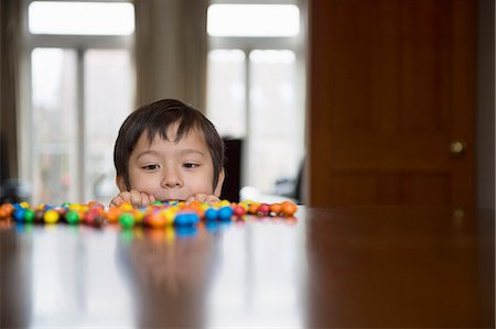 sweets - Boy peering over table at candy Stock Photo - Premium Royalty-Free, Code: 614-07587639