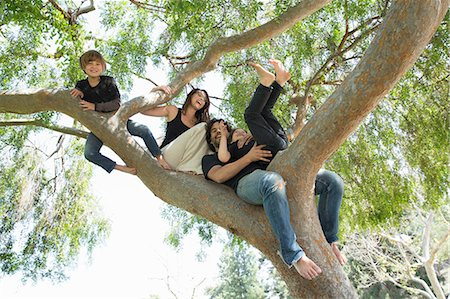 Portrait of family with two boys climbing on park tree Stock Photo - Premium Royalty-Free, Code: 614-07587700