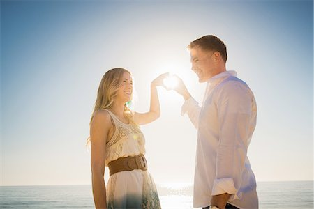 Young couple making a heart in front of sun with hands Stock Photo - Premium Royalty-Free, Code: 614-07652175
