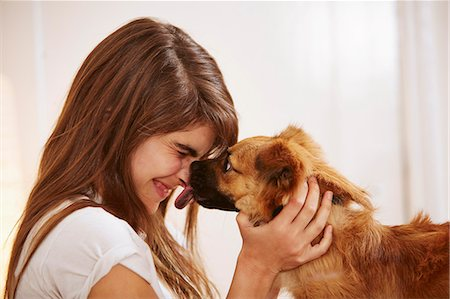 dog and woman and love - Young woman having face licked by pet dog Stock Photo - Premium Royalty-Free, Code: 614-07652178