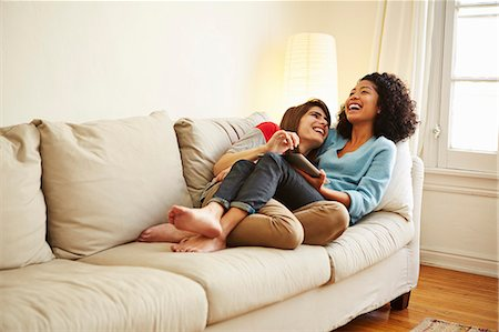 Young female couple reclining on sofa looking at digital tablet Stock Photo - Premium Royalty-Free, Code: 614-07652187