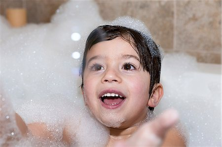 Young boy trying to catch bubble in bubble bath Stock Photo - Premium Royalty-Free, Code: 614-07652190