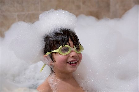 Portrait of young boy wearing goggles in bubble bath Stock Photo - Premium Royalty-Free, Code: 614-07652191