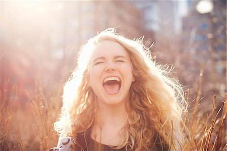 Young woman in long grass with open mouth Stock Photo - Premium Royalty-Free, Code: 614-07652218