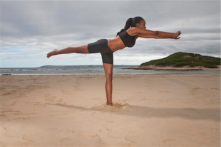 Young woman practicing yoga on one leg at beach Stock Photo - Premium Royalty-Free, Code: 614-07652234