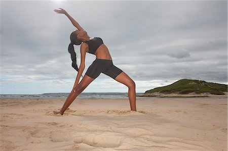 Young woman practicing yoga position on beach Stock Photo - Premium Royalty-Free, Code: 614-07652235