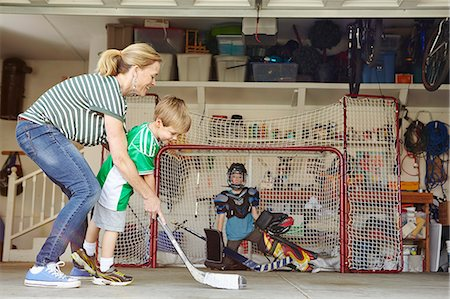 sports and hockey - Mother playing hockey in garage with two sons Stock Photo - Premium Royalty-Free, Code: 614-07652251