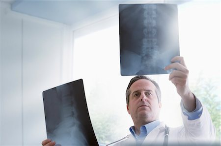 spinal column - Doctor studying x-rays Stock Photo - Premium Royalty-Free, Code: 614-07652266