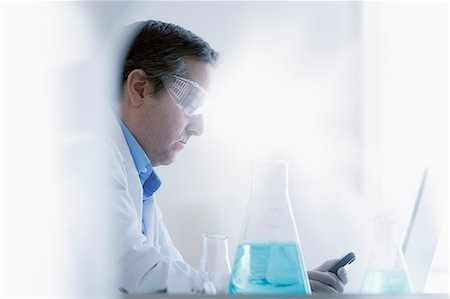 device - Scientist looking at smartphone Stock Photo - Premium Royalty-Free, Code: 614-07652260
