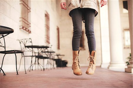 Young woman waist down jumping next to sidewalk cafe Stock Photo - Premium Royalty-Free, Code: 614-07652274