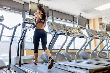 Mid adult woman running on treadmill in gym Stock Photo - Premium Royalty-Free, Code: 614-07652288