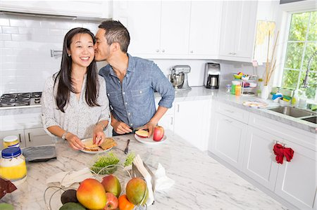 sin autorización de la propiedad - Romantic mid adult couple preparing sandwich at kitchen counter Foto de stock - Sin royalties Premium, Código: 614-07652357