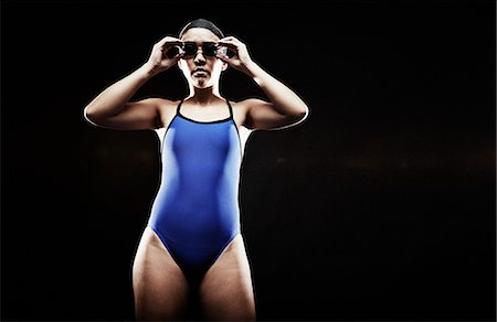 swimming - Young woman wearing blue swimsuit putting on goggles Stock Photo - Premium Royalty-Free, Code: 614-07652397