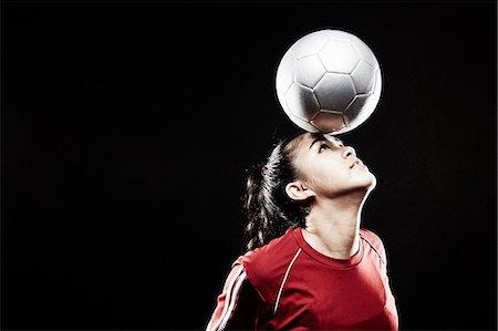 footballeur - Young woman balancing football on forehead Stock Photo - Premium Royalty-Free, Code: 614-07652390