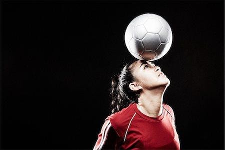 footballeur - Young woman balancing football on forehead Stock Photo - Premium Royalty-Free, Code: 614-07652390