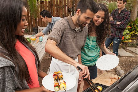 Friends sitting around table sharing barbecue food Stock Photo - Premium Royalty-Free, Code: 614-07652465