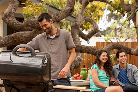 Man cooking on barbecue, friends in background Stock Photo - Premium Royalty-Free, Code: 614-07652461