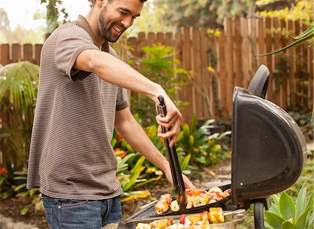 Man cooking vegetable skewers on barbecue Stock Photo - Premium Royalty-Free, Code: 614-07652463
