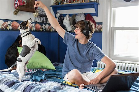 Teenage boy sitting on bed with laptop computer, playing with dog Stock Photo - Premium Royalty-Free, Code: 614-07652473
